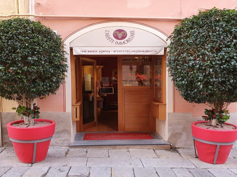 L'entrata dell'agenzia immobiliare identificata da due grandi vasi rossi